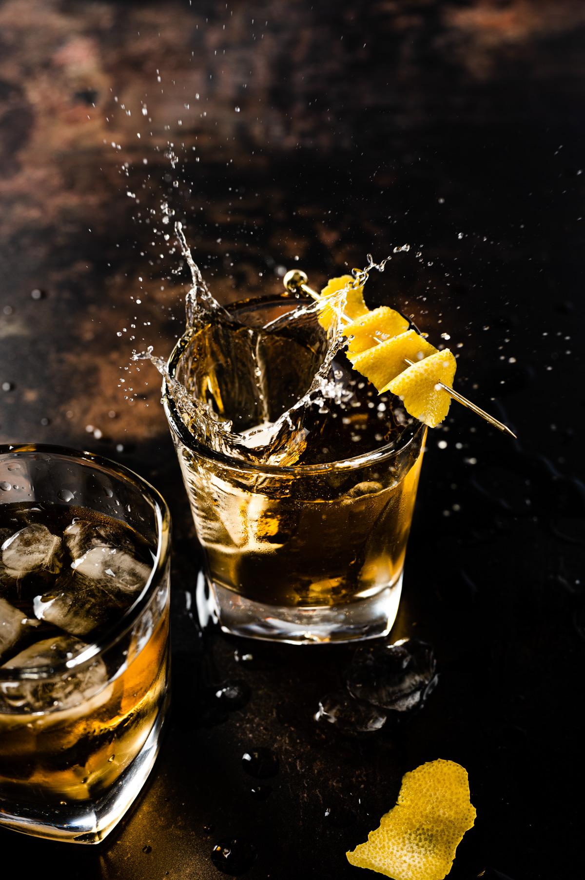 Whisky Glass with a lemon garnish on dark background with a splash